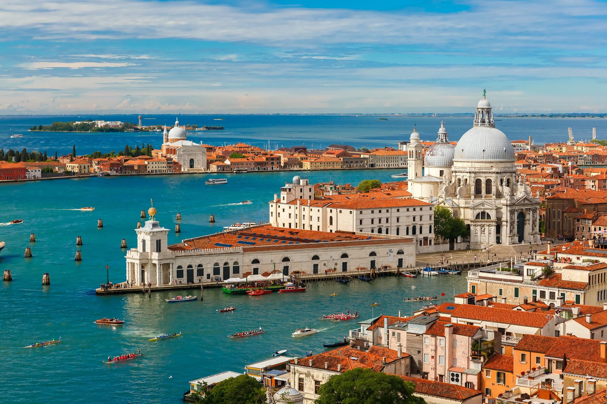 View from Campanile di San Marco to Grand Canal and Basilica di Santa Maria della Salute during Vogalonga regatta at summer morning in Venice, Italy
